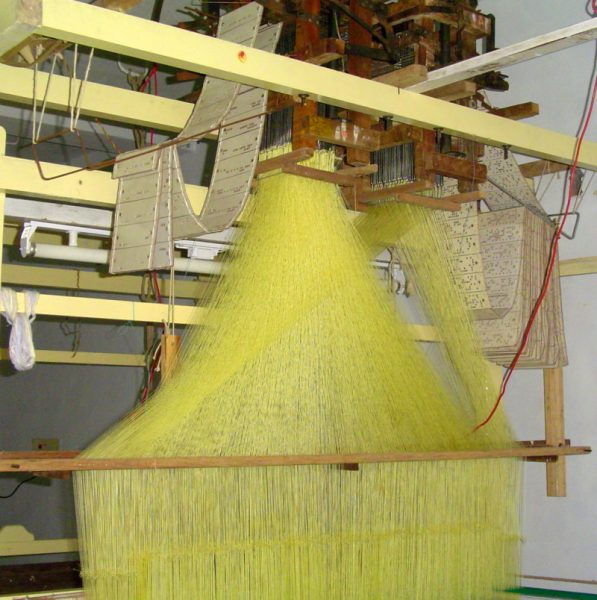 The traditional loom for making Kanchipuram sari. Those white cards with holes in it defines the patterns/designs in the Sari. Also seen is the yellow silk thread that fanning out from the top of the loom.